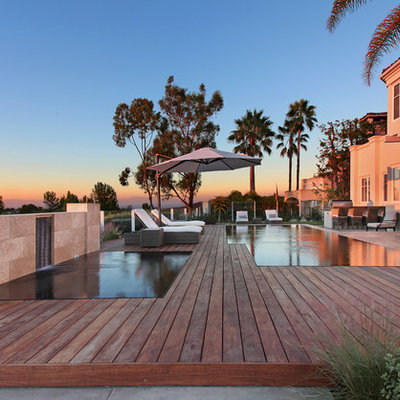 Inspiration for a mid-sized contemporary backyard custom-shaped infinity pool fountain remodel in Orange County with decking