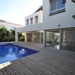 Ispirazione per una piscina minimalista rettangolare dietro casa con pedane