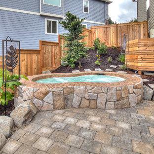 Foto de piscinas y jacuzzis clásicos, grandes, tipo riñón, en patio trasero, con adoquines de hormigón
