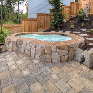 Modelo de piscinas y jacuzzis clásicos, grandes, tipo riñón, en patio trasero, con adoquines de hormigón