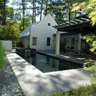 Example of a minimalist backyard stamped concrete and rectangular pool design in Atlanta