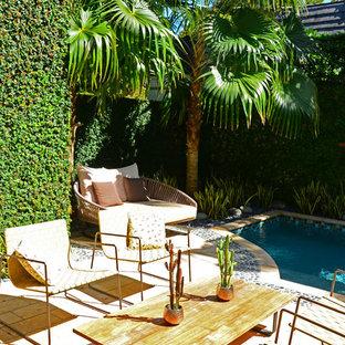 Esempio di una piscina monocorsia etnica rettangolare di medie dimensioni e dietro casa con una vasca idromassaggio e pavimentazioni in cemento