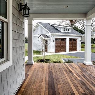 Bild på en mellanstor amerikansk veranda framför huset, med trädäck och takförlängning