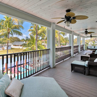 This is an example of a large coastal back porch design in Miami with decking and a roof extension.