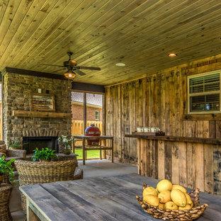 Foto di un grande portico country dietro casa con un portico chiuso, lastre di cemento e un tetto a sbalzo