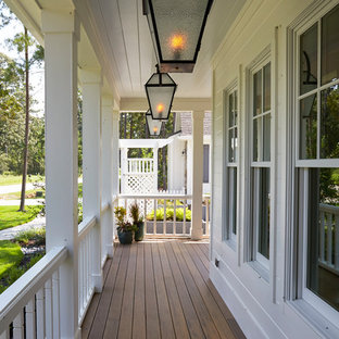 Large elegant front porch photo in Houston with a roof extension