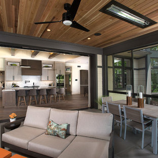 Large minimalist stone screened-in back porch idea in Grand Rapids with a roof extension
