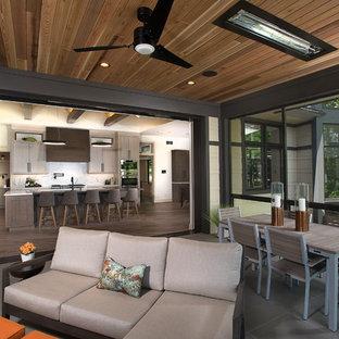 Idee per un grande portico minimalista dietro casa con un portico chiuso, pavimentazioni in pietra naturale e un tetto a sbalzo