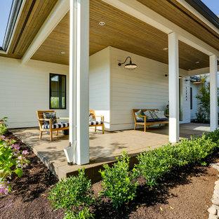 Immagine di un ampio portico country davanti casa con un tetto a sbalzo