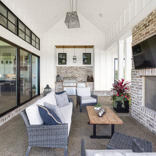 Imagen de terraza campestre, grande, en patio lateral y anexo de casas, con fuente y losas de hormigón