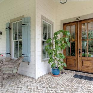 Foto di un portico country di medie dimensioni e davanti casa con pavimentazioni in mattoni e un tetto a sbalzo