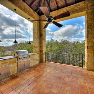 Design ideas for a large mediterranean back veranda in Austin with an outdoor kitchen, tiled flooring and a roof extension.