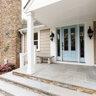 This is an example of a mid-sized traditional front porch design in Boston with a roof extension.