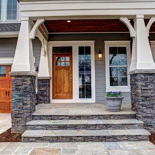 Idee per un portico stile americano di medie dimensioni e davanti casa con un giardino in vaso, pavimentazioni in pietra naturale e un tetto a sbalzo