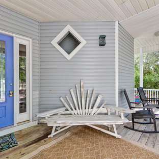 Inspiration for a beach style front porch remodel in Miami with decking and a roof extension