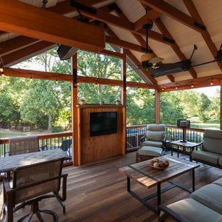Idee per un patio o portico rustico dietro casa con un portico chiuso e un tetto a sbalzo