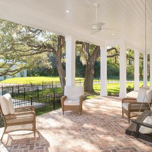 Imagen de terraza clásica renovada, grande, en patio delantero y anexo de casas, con adoquines de ladrillo