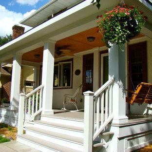 Immagine di un portico classico davanti casa e di medie dimensioni con pedane e un tetto a sbalzo
