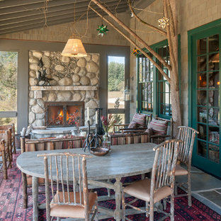 Huge mountain style screened-in porch idea in Grand Rapids with a roof extension