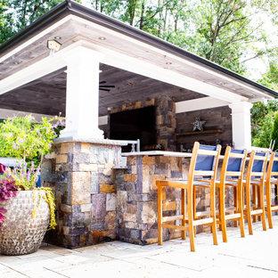 Esempio di un portico rustico di medie dimensioni e dietro casa con un caminetto, pavimentazioni in pietra naturale e un tetto a sbalzo