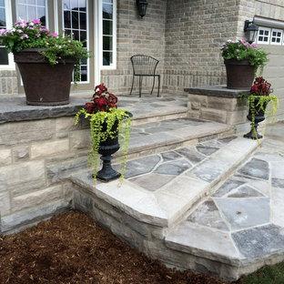 Immagine di un patio o portico chic di medie dimensioni e davanti casa con pavimentazioni in pietra naturale e un tetto a sbalzo