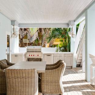 Idee per un portico stile marinaro dietro casa con pavimentazioni in mattoni e un tetto a sbalzo