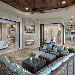 Idée de décoration pour un grand porche arrière méditerranéen avec un foyer extérieur, une extension de toiture et des pavés en pierre naturelle.