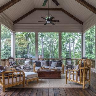 Immagine di un ampio portico stile americano dietro casa con un portico chiuso e un tetto a sbalzo