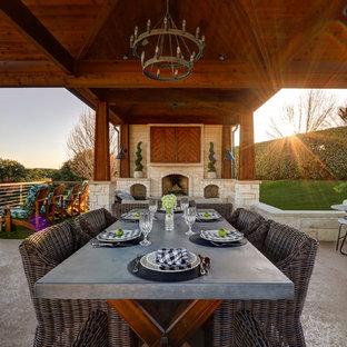 Imagen de terraza mediterránea, grande, en patio trasero, con chimenea y losas de hormigón