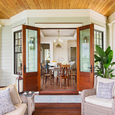 This is an example of a coastal screened-in porch design in Charleston with decking and a roof extension.