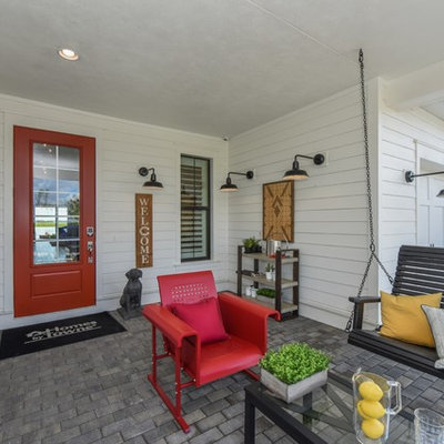 Cottage brick porch photo in Milwaukee with a roof extension
