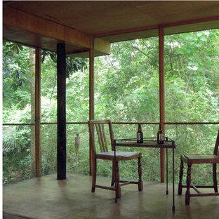 Idee per un piccolo portico etnico dietro casa con un portico chiuso e un tetto a sbalzo