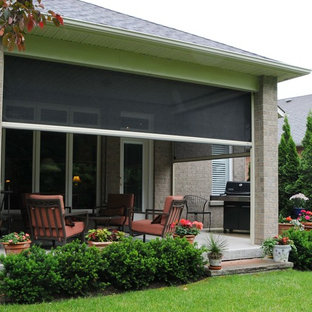 This is an example of a small traditional concrete screened-in front porch design in Toronto with a roof extension.