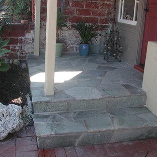 Foto di un piccolo portico stile americano davanti casa con un giardino in vaso, pavimentazioni in pietra naturale e un tetto a sbalzo