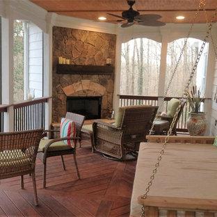 Esempio di un portico design dietro casa e di medie dimensioni con un focolare, pedane e un tetto a sbalzo