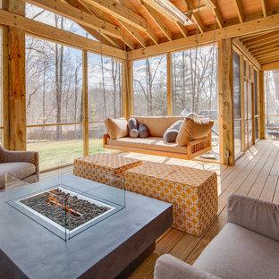 Inredning av en lantlig mycket stor innätad veranda på baksidan av huset, med trädäck och takförlängning
