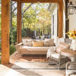 Idéer för en mycket stor lantlig veranda framför huset, med trädäck och takförlängning
