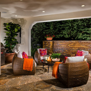 Tuscan stone porch idea in Los Angeles with a roof extension