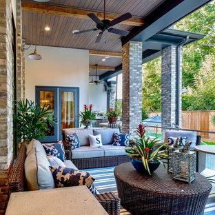 Ispirazione per un grande portico chic dietro casa con un caminetto, pavimentazioni in pietra naturale e un tetto a sbalzo