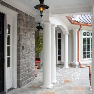 Foto di un ampio portico eclettico davanti casa con un giardino in vaso, cemento stampato e un tetto a sbalzo