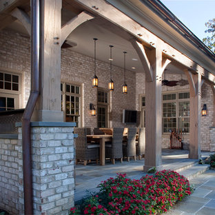 Huge classic stone porch idea in Richmond with a roof extension