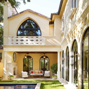 Inspiration for a mediterranean back porch remodel in Dallas with a fireplace and a roof extension