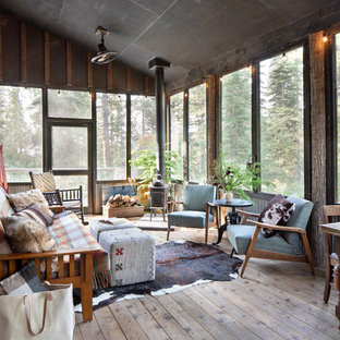 This is an example of a rustic screened-in side porch design in Other with decking and a roof extension.