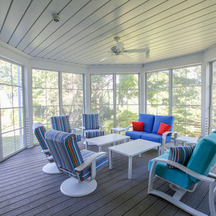 This is an example of a coastal screened-in back porch design in Grand Rapids with decking and a roof extension.