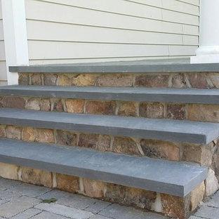 Ispirazione per un portico tradizionale di medie dimensioni e davanti casa con pavimentazioni in pietra naturale e un tetto a sbalzo