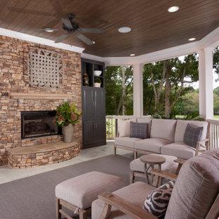 Ispirazione per un grande portico chic dietro casa con un caminetto, piastrelle e un tetto a sbalzo