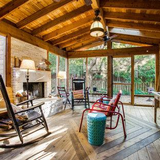 Foto di un grande patio o portico rustico con un portico chiuso, pedane e un tetto a sbalzo
