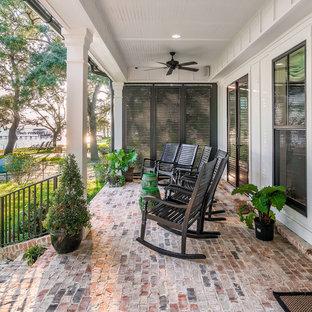 Esempio di un portico dietro casa con pavimentazioni in mattoni e un tetto a sbalzo