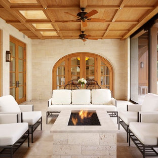 This is an example of a mediterranean porch design in Austin with a fire pit and a roof extension.