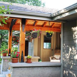 Ispirazione per un portico american style di medie dimensioni con un tetto a sbalzo e lastre di cemento